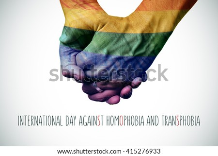 closeup of a gay couple holding hands patterned as the rainbow flag and the text international day against homophobia and transphobia - stock photo