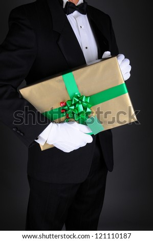 Closeup of a gentleman in a tuxedo holding a Christmas present under his arm. Vertical format on a light to dark gray background. Man is unrecognizable. - stock photo