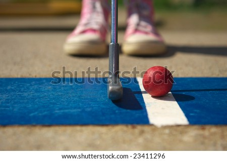 Closeup of a girl in pink trainers getting ready to putt. - stock photo