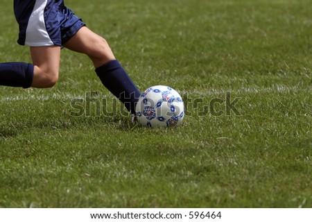 Closeup of a girl kicking a soccer ball during a soccer game. - stock photo