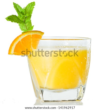 closeup of a glass filled with fresh orange juice garnished with an orange slice and fresh mint isolated on a white background - stock photo