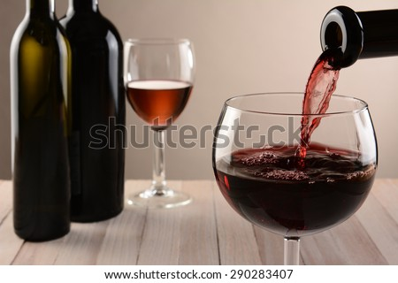 Closeup of a glass of wine and a bottle pouring. Out of focus wine bottles and another wineglass are in the background. Horizontal still life with warm tones and light to dark background lighting. - stock photo