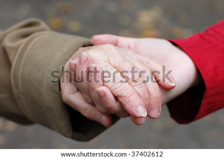 closeup of a grandfather holding his grand daughter hand - stock photo
