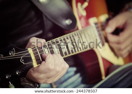 closeup of a guitar player in vintage tone - stock photo