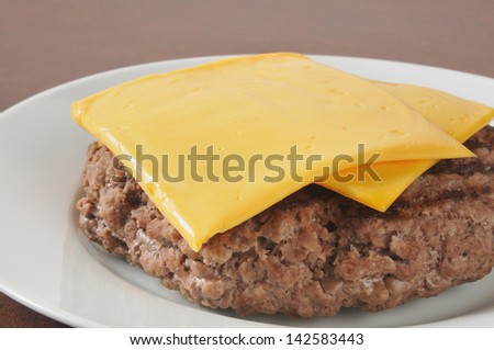 Closeup of a hamburger patty with sliced cheese - stock photo