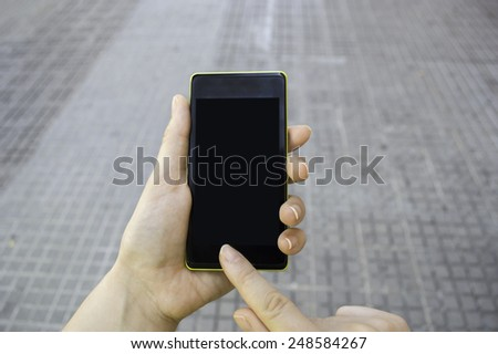 closeup of a hand using a smart phone on the street - stock photo