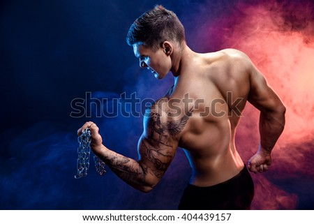 Closeup of a handsome power athletic man bodybuilder doing exercises with chain. Fitness muscular body on dark background. Perfect male. Awesome bodybuilder, tattoo, posing.  - stock photo