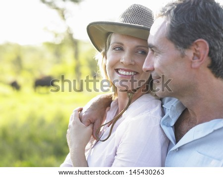 Closeup of a happy adult couple against blurred meadow - stock photo