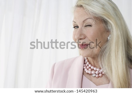 Closeup of a happy and glamorous senior woman winking against white background - stock photo
