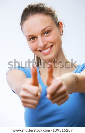 Closeup of a happy young woman showing thumb's up sign - stock photo