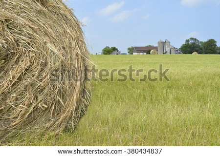 Closeup of a hay roll in a field in the country, with a blurred barn in the far background. - stock photo
