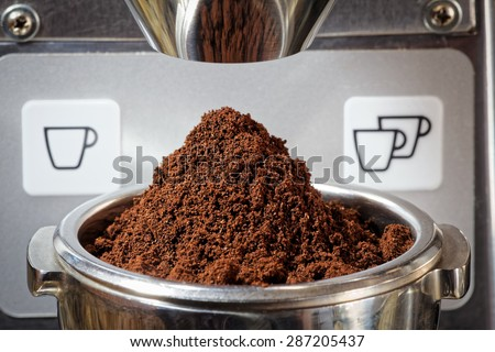 Closeup of a heap of freshly ground coffee beans for an espresso. The finely ground coffee is in the metal portafilter. The image is taken with the portafilter under the metal chute of the grinder - stock photo