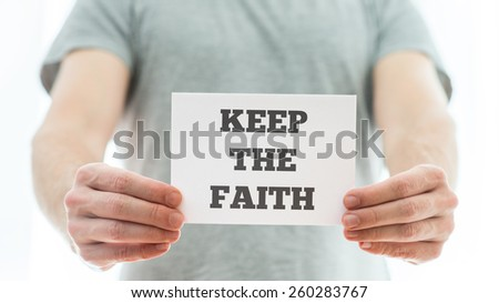 Closeup of a homeless man holding up white card with a motivational message Keep the faith. - stock photo