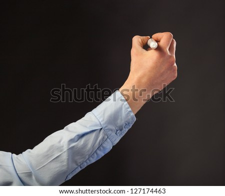 Closeup of a human hand writing with marker on grey background; copy space - stock photo