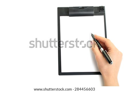 Closeup of a human hand writing with pen on clipboard; copy space - stock photo