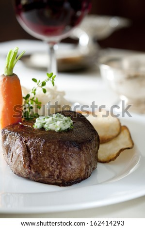 Closeup of a juicy tenderloin steak with potatoes and carrot. - stock photo