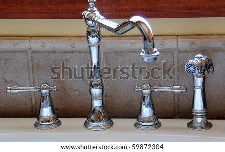 Closeup of a kitchen sink faucet and handles - stock photo
