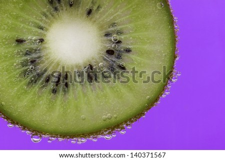 Closeup of a kiwi slice covered in water bubbles against a purple background - stock photo