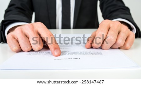 Closeup of a lawyer or a real estate agent proofreading Terms and conditions document. - stock photo