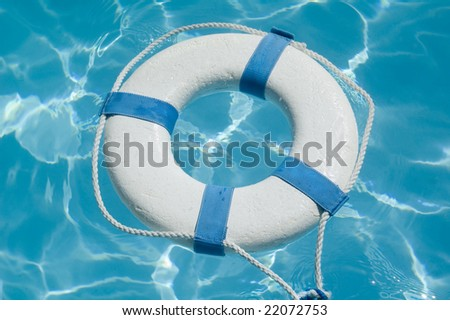 Closeup of a life preserver ring floating on beautiful blue water - stock photo