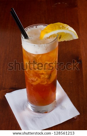 closeup of a long island red tea served on a dark bar top garnish with a lemon - stock photo