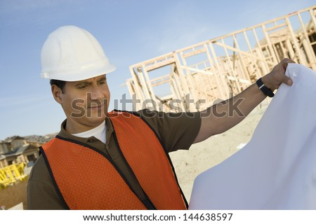 Closeup of a male construction worker with blueprints at site - stock photo
