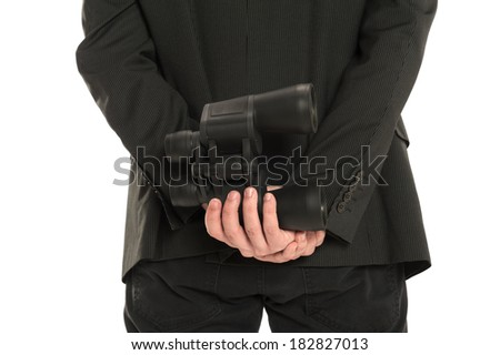 Closeup of a man holding a pair of binoculars behind his back, isolated on white - stock photo