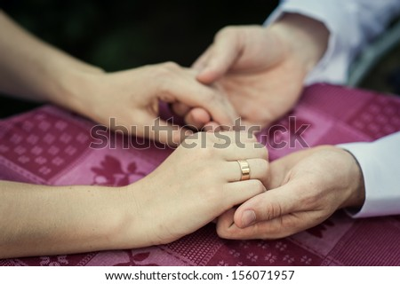 Closeup of a man holding his girlfriend's hand at the restaurant. Romantic Couple Holding Each Other's Hand At Dinner In An Restaurant. man's and woman's hands on the table in cafe. - stock photo