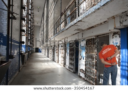 Closeup of a man in prison using a hacksaw to escape from his handcuffs - stock photo