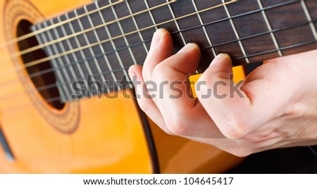 Closeup of a man's fingers playing the guitar - stock photo