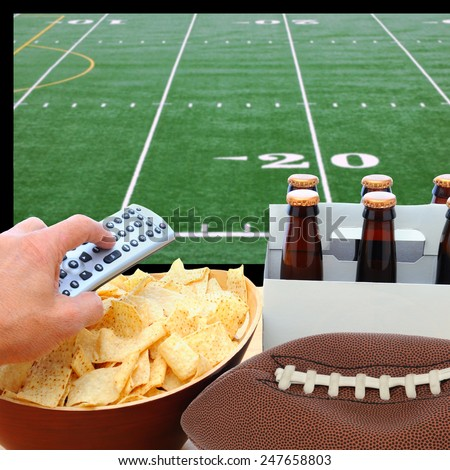 Closeup of a man's hand holding a TV remote with a bowl of chips and a six pack of beer with a deflated football. The TV screen has a football field with remote pointed at the screen. - stock photo