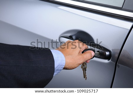 Closeup of a man's hand inserting a key into the door lock of a car. Horizontal format. Car and man are unrecognizable. - stock photo