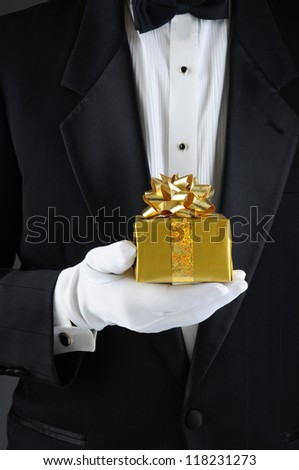 Closeup of a man wearing a tuxedo holding a Christmas present in front of his body. Vertical format. Man is unrecognizable. - stock photo