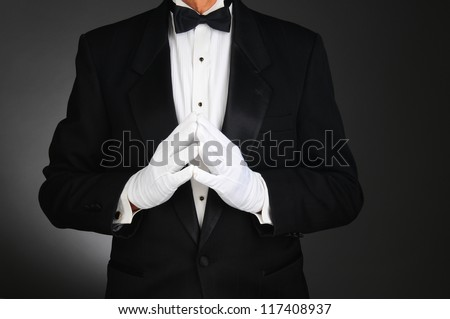 Closeup of a man wearing a tuxedo with his hands together in front of his torso. Man is unrecognizable. Horizontal format on a light to dark gray background. - stock photo