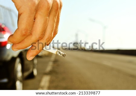 closeup of a man with a burning cigarette in his hand while is waiting besides a car parked next to a no traffic road - stock photo