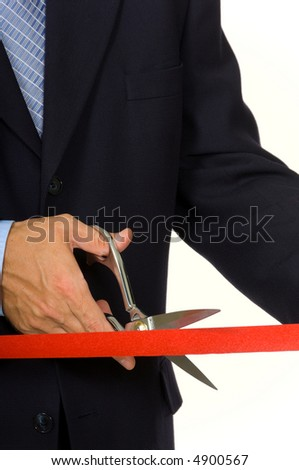 Closeup of a mans hand in a blue business suit cutting a red ribbon with shiny scissors- focus on ribbon - stock photo