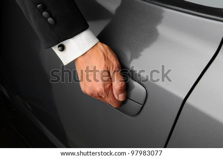 Closeup of a mans hand on the latch of a car door. The valet is wearing a tuxedo. - stock photo