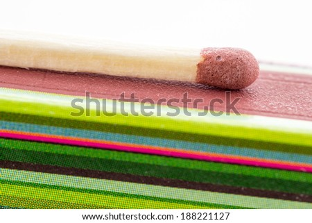 Closeup of a match with a box, colors and lines - stock photo