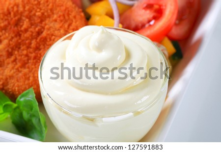 Closeup of a mayonnaise swirl in a glass cup - stock photo