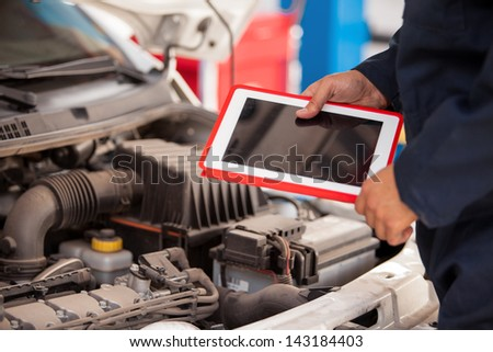 Closeup of a mechanic using a tablet computer next to an open hood in an auto shop - stock photo