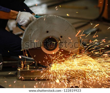 Closeup of a metal cutting saw slicing through a steel pipe. - stock photo