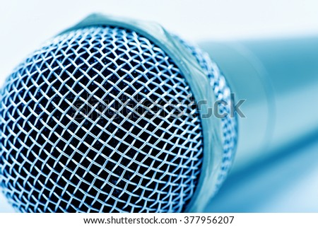 closeup of a microphone, in a blue toning - stock photo