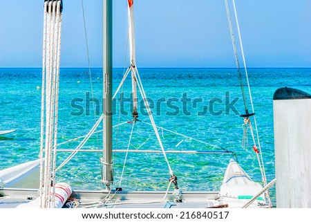 Closeup of a moored white catamaran sailboat against a calm blue tropical ocean under summer sunshine - stock photo