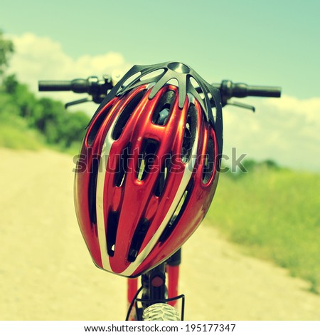 closeup of a mountain bike with a red helmet on a dirt road - stock photo