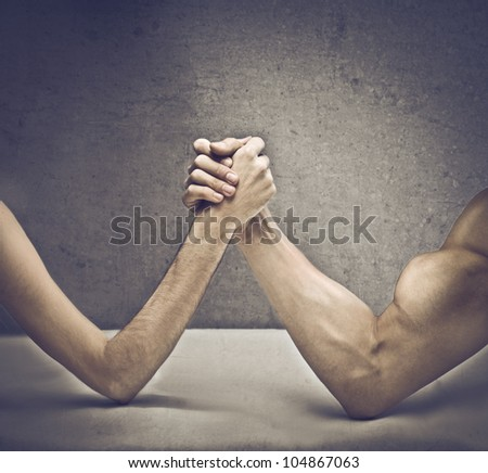 Closeup of a muscular man playing arm wrestling with a skinny one - stock photo