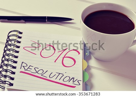 closeup of a notebook with the text 2016 resolutions written in it and a cup of coffee on a white table - stock photo