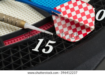 Closeup of a old used darts board with a dart - stock photo