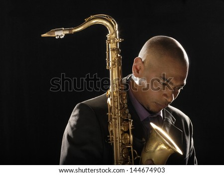 Closeup of a pensive man with saxophone looking down against black background - stock photo