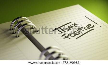 Closeup of a personal agenda setting an important date representing a time schedule. The words Think positive written on a white notebook to remind you an important appointment. - stock photo