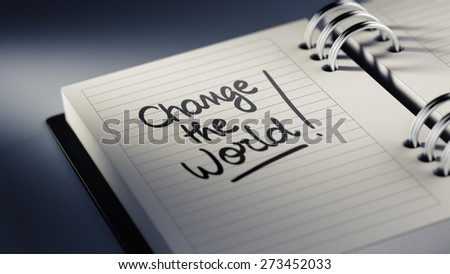 Closeup of a personal agenda setting an important date representing a time schedule. The words Change the world written on a white notebook to remind you an important appointment. - stock photo